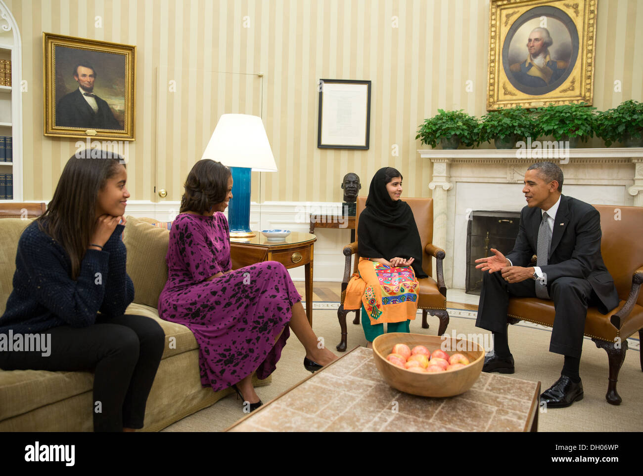 President Barack Obama, First Lady Michelle Obama, and their daughter Malia meet with Malala Yousafzai, the young Pakistani schoolgirl who was shot in the head by the Taliban a year ago, in the Oval Office, Oct. 11, 2013. - Stock Image
