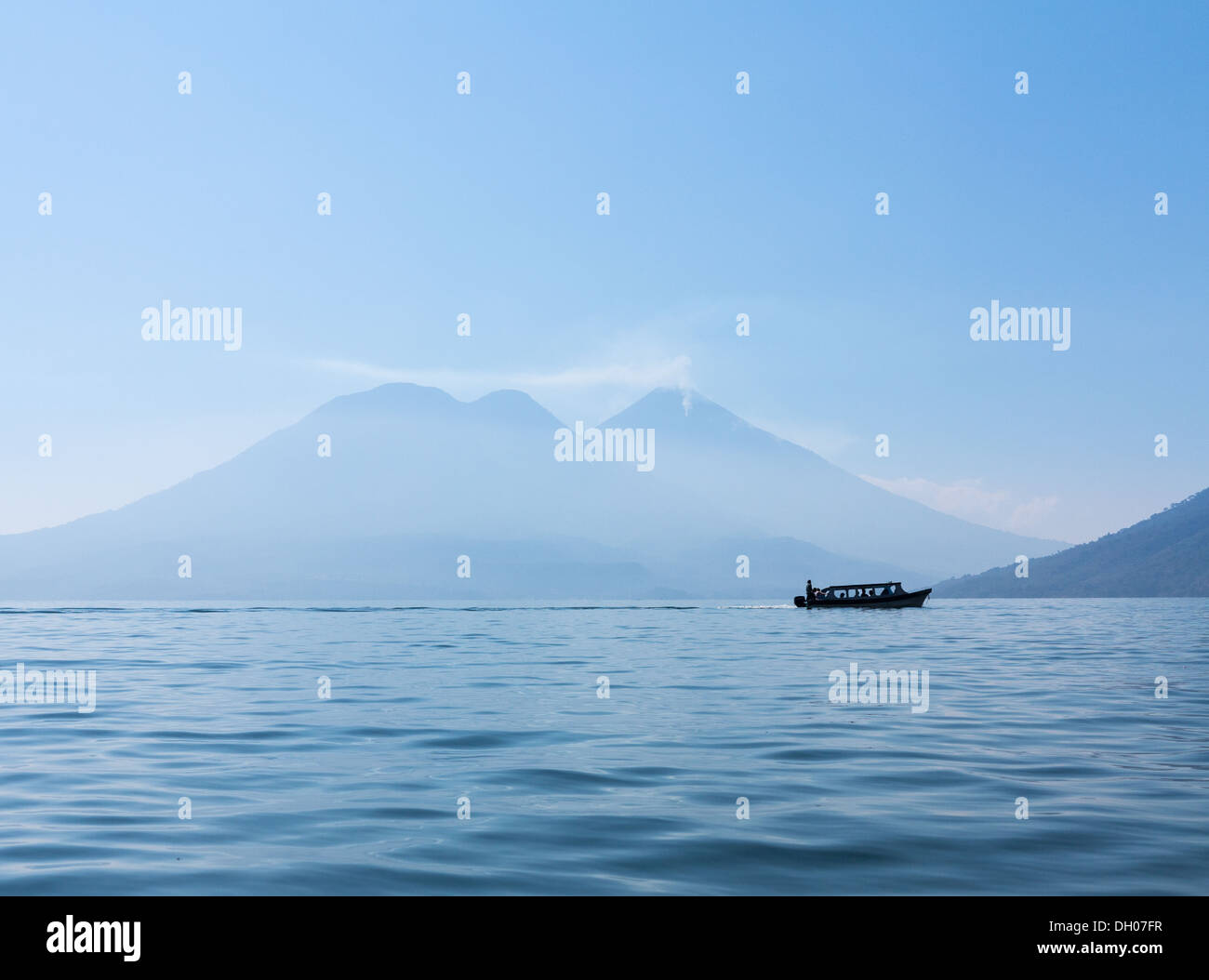 Sunrise at Lake Atitlan in Guatemala - formed from volcano crater. With tourist boat or cruiser in the distance - Stock Image