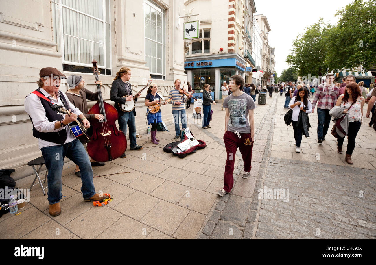 People walking past a folk band busking on the street, Norwich, Norfolk, UK - Stock Image