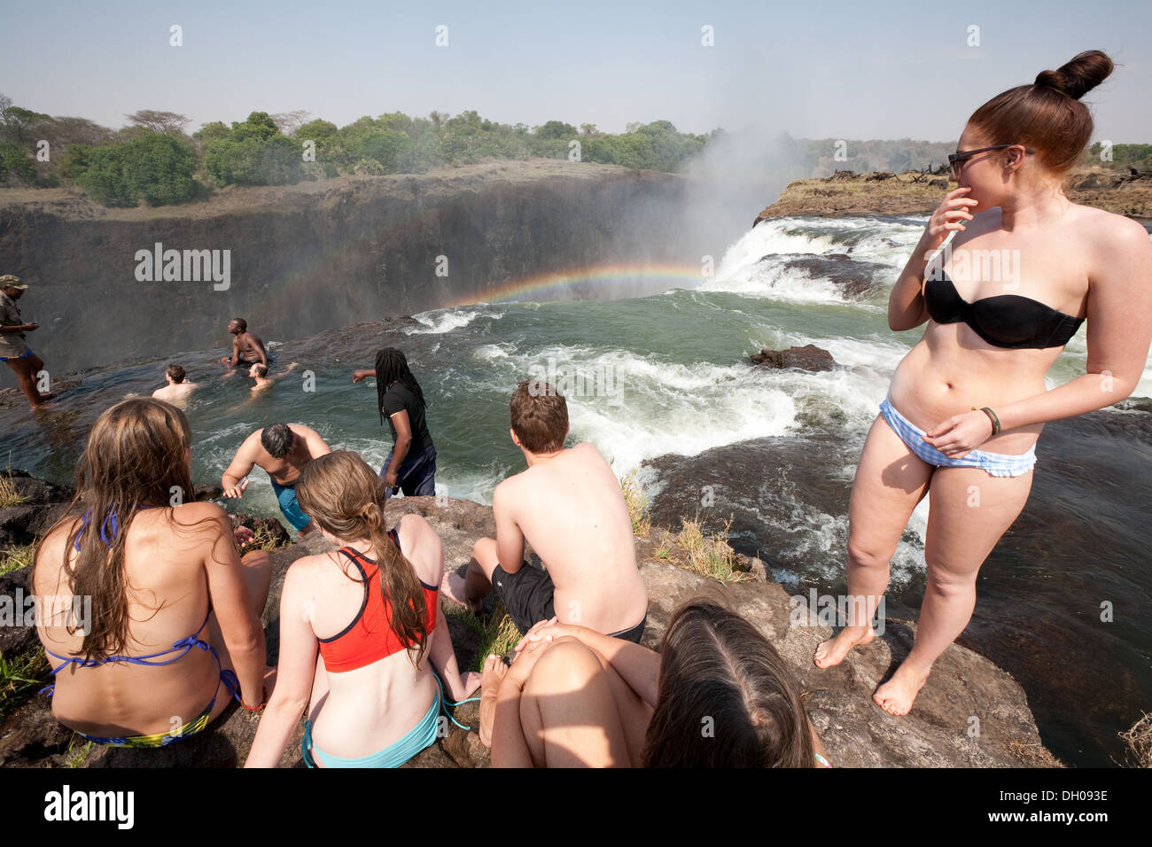 Tourists swimming in Devils Pool at the edge of Victoria falls, Livingstone Island, Zambia Africa - Stock Image