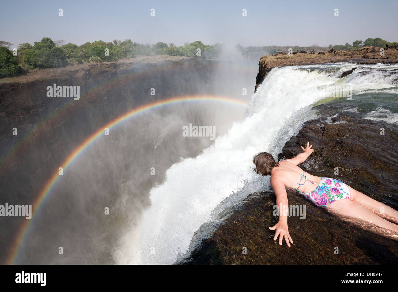 Middle aged caucasian woman looking over the edge of Victoria Falls in Devils Pool, example of adventure holiday, Stock Photo