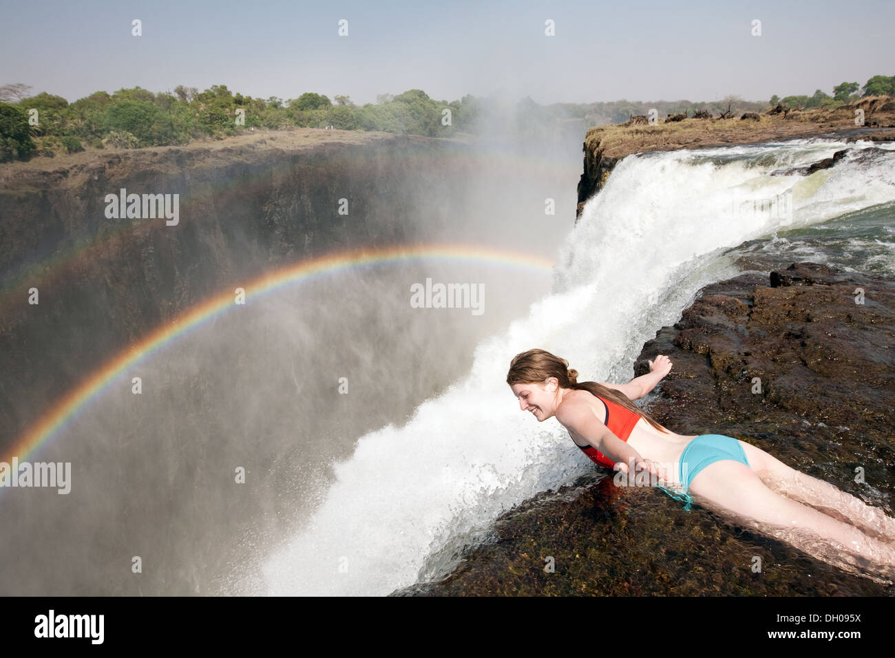 a young woman hanging over the edge of the victoria falls in devils