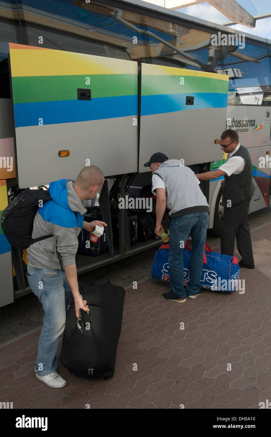 swebus sweden bus coach buses coaches luggage people loading bags baggage bag into the lockers of a modern coach - Stock Image