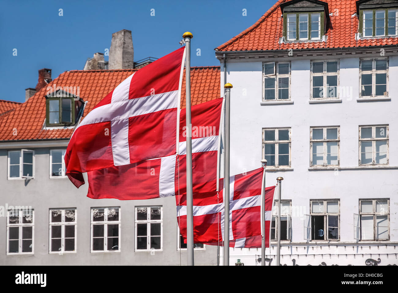 Danish flag waving, in the Nyhavn district of Copenhagen, Denmark - Stock Image