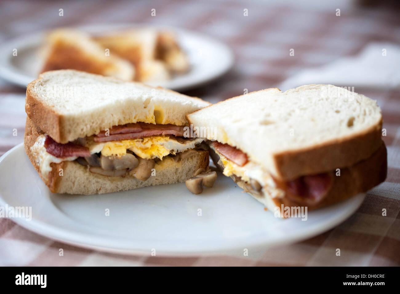 Bacon, egg and mushroom sandwich, British food. - Stock Image
