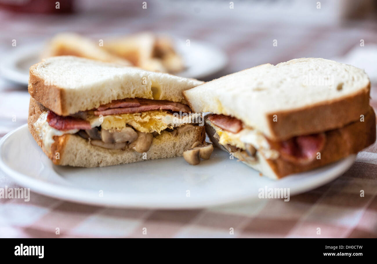 A halved bacon, egg and mushroom sandwich on a plate, London, England, UK. - Stock Image
