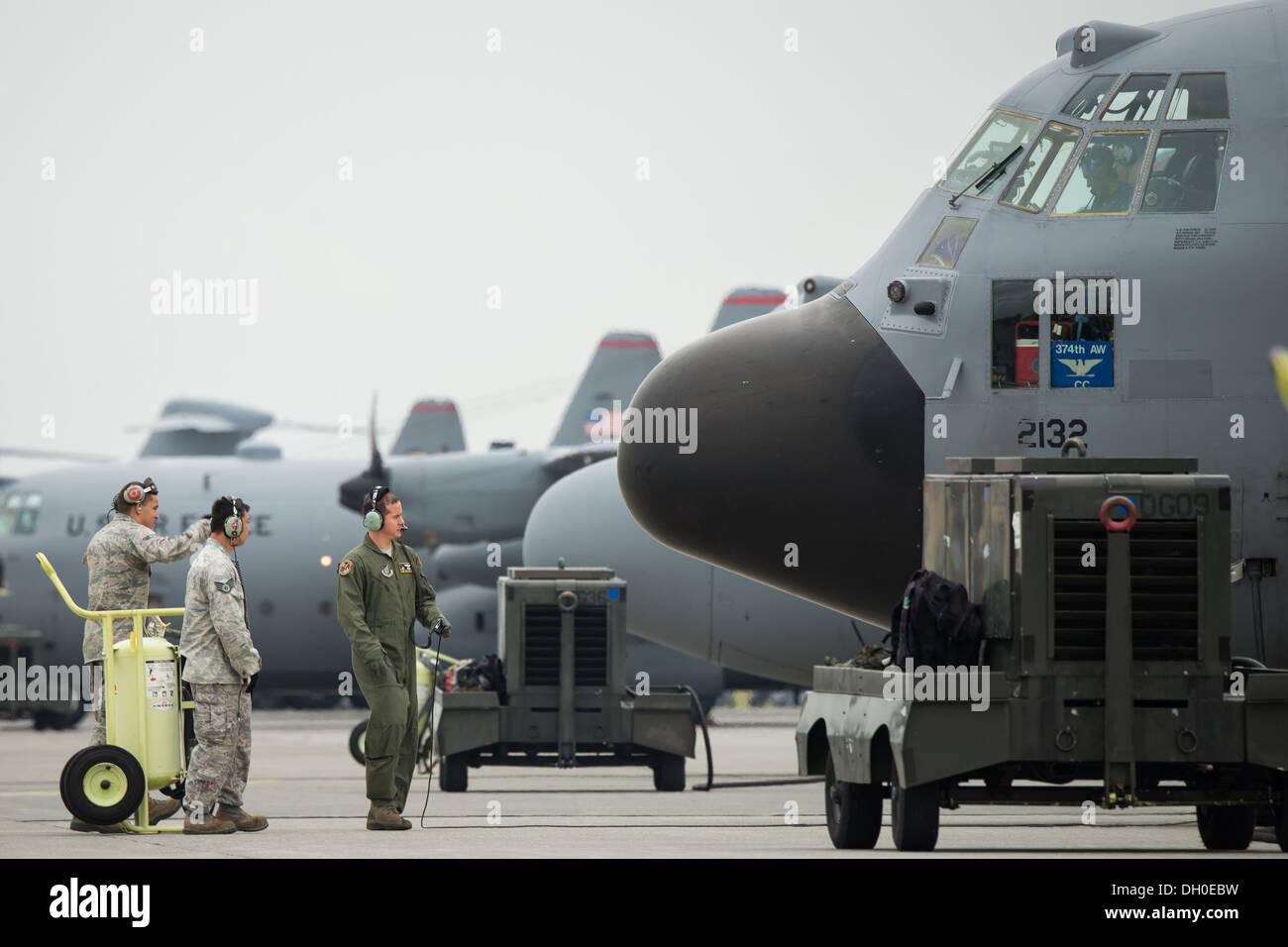 Airmen perform a preflight inspection by a C-130 Hercules at Yokota Air Base, Japan, Oct. 22, 2013. Ten C-130 Hercules from the - Stock Image