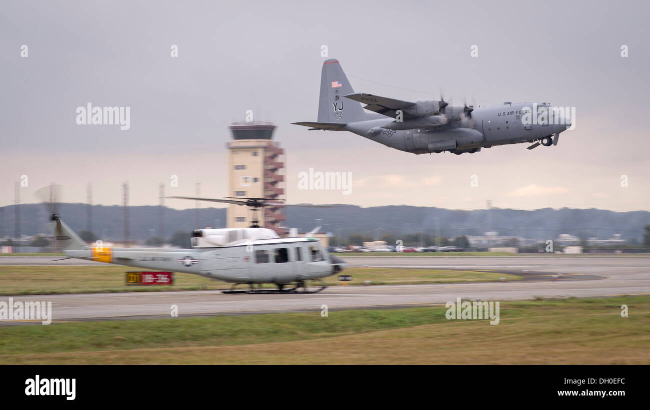 A C-130 Hercules takes off past a UH-1 Huey during a large-formation mission at Yokota Air Base, Japan, Oct. 22, 2013. During this mission, Team Yokota launched every aircraft currently stationed at Yokota. - Stock Image