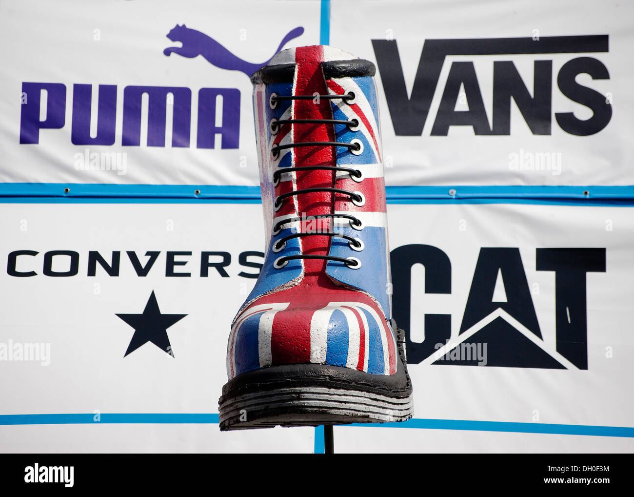 Giant larger than life replica Dr martin boot with union flag design with logo's of Puma Vans Converse Cat printed behind - Stock Image