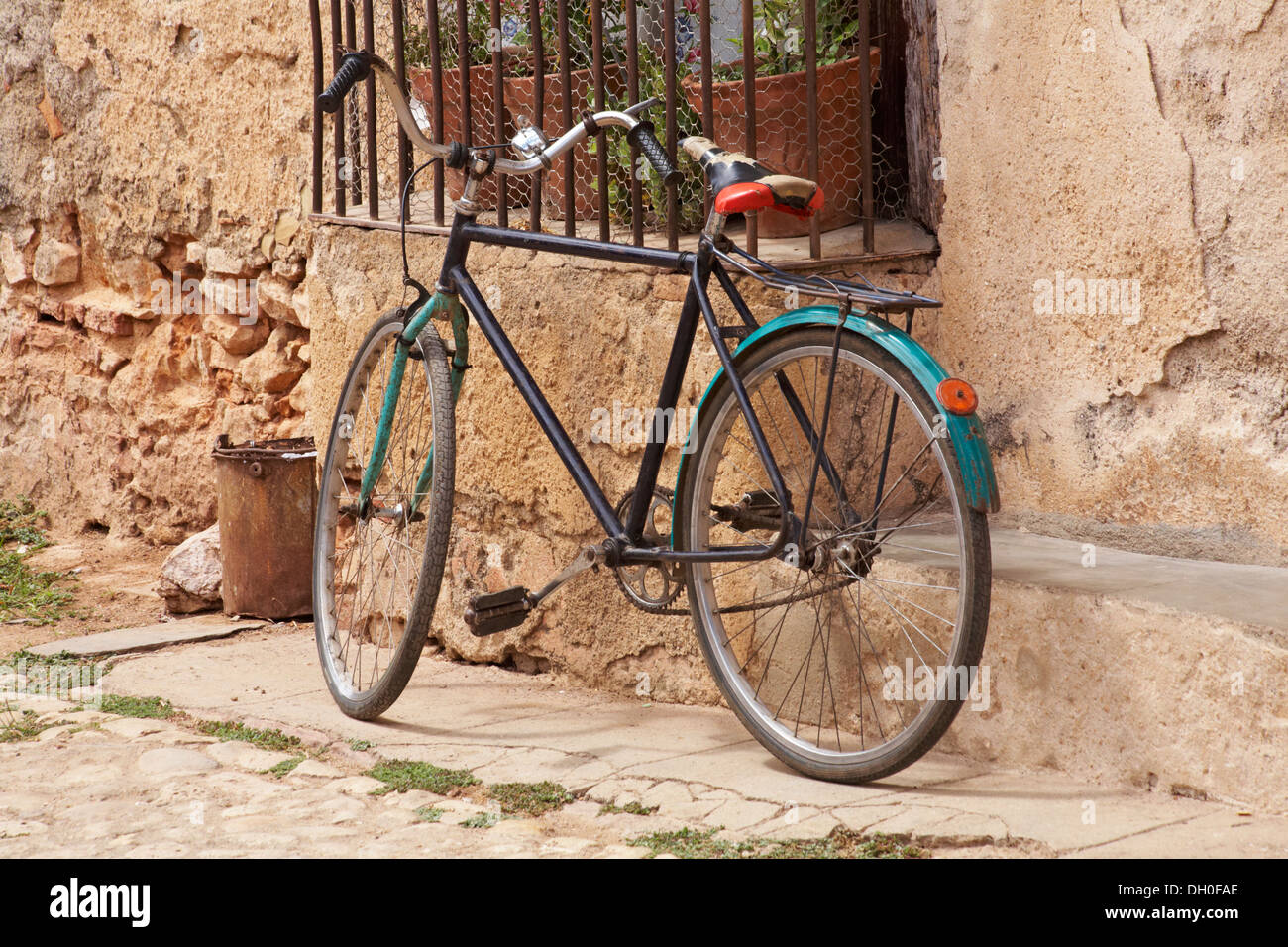 bicycle leant against railings at Trinidad, Cuba, West Indies, Caribbean, Central America in March - Stock Image