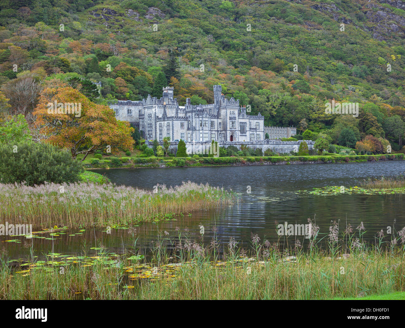 County Galway, Ireland: Kylemore Abbey sheltered by the slopes of the Twelve Bens on the shoreline of Kylemore Lough - Stock Image