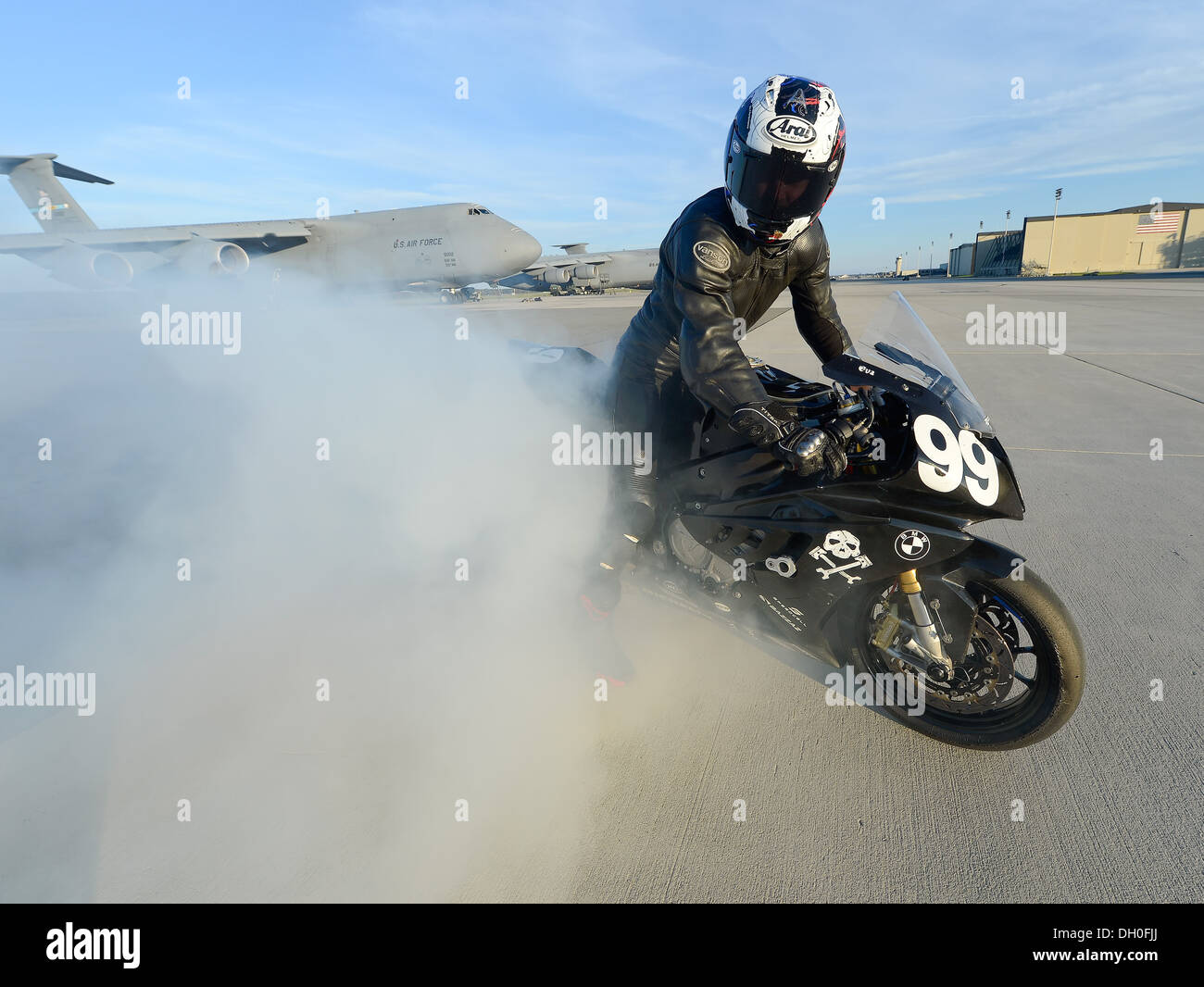 Sam Fleming, Army of Darkness motorcycle endurance racing team team leader, smokes the rear tire during a demonstration of power of the BMW S1000RR, number 99, during a visit to Dover Air Force Base, Del. on Oct. 21, 2013. The team interacted with Team Do - Stock Image