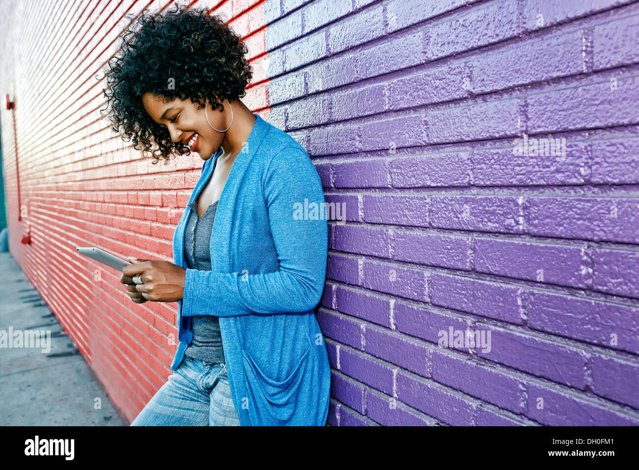 Mixed race woman with cell phone standing by colorful wall Stock Photo