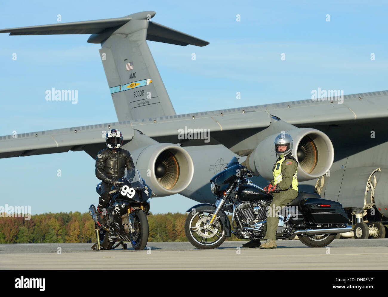 Sam Fleming, Army of Darkness motorcycle endurance racing team team leader (left), sits on a BMW S1000RR, number 99, wearing full racing safety gear while Technical Sgt. David Grant of the 3rd Airlift Squadron sits on a Harley Davidson Street Glide Specia - Stock Image