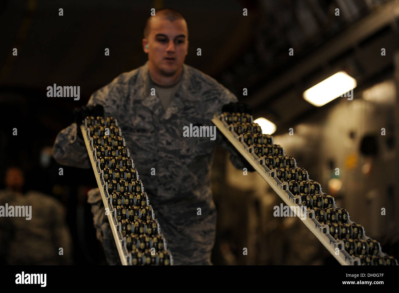 U.S. Air Force Staff Sgt. Craig Grabowski, 633rd Logistics Readiness Squadron air terminal supervisor, lifts rolling lanes from - Stock Image