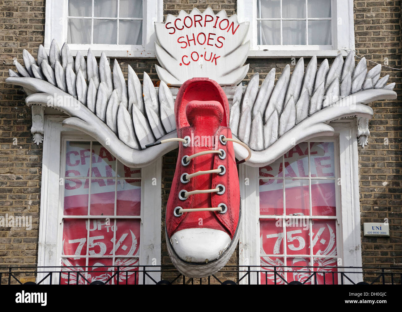 scorpion shoes, larger than life, red trainer shoe's, with wings, attached, to the side of shop front, building, - Stock Image