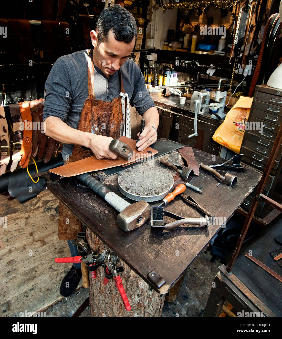 leather worker,Man crafting leather, hand made, leather goods. - Stock Image