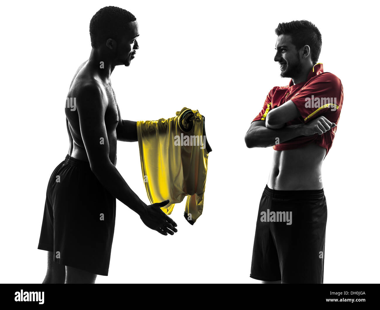 two men soccer player playing football competition exchanging jersey in silhouette on white background - Stock Image