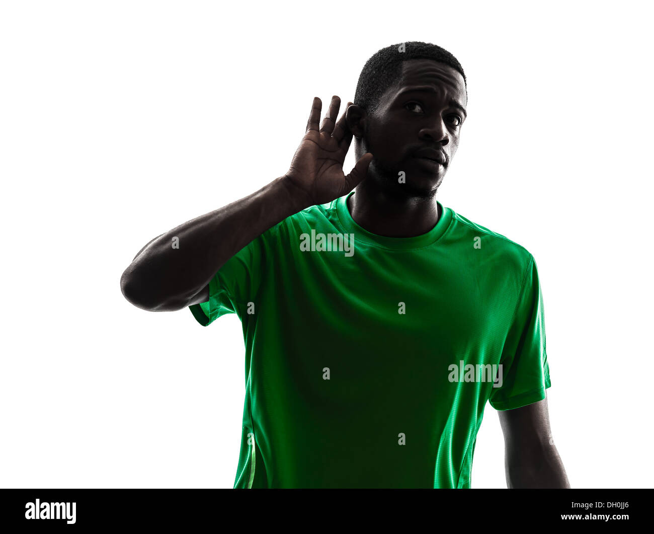 one african man soccer player green jersey hearing gesture in silhouette on white background - Stock Image