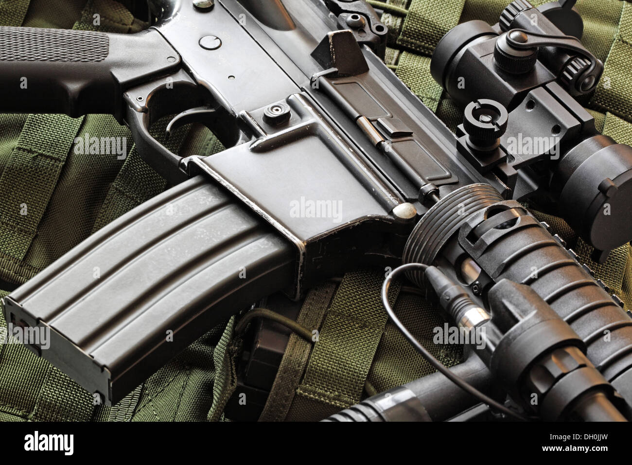 Close-up of a scratched M4A1 (AR-15) carbine and green military tactical vest - Stock Image