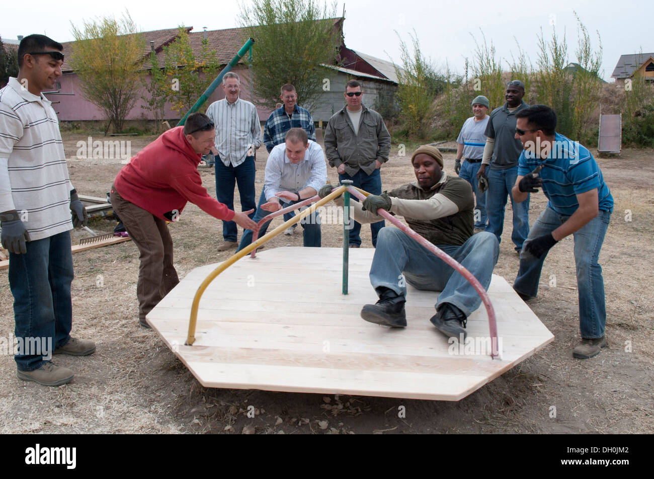 Members of the 'Manas Top 3' and Transit Center at Manas, Kyrgyzstan, try out a refurbished merry-go-round at the Nadyezhda Children's Rehabilitation Center playground in Bishkek, Oct. 23, 2013. The 'Manas Top 3' is partnered with the rehabilitation cente - Stock Image
