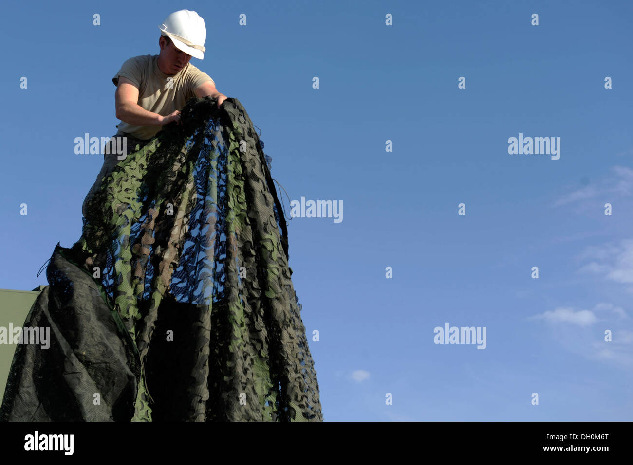 A U.S. Air Force Airman removes camouflage netting at Hill Air Force Base, Utah, Oct. 24, 2013. The Airman is assigned to the 729th Air Control Squadron who are currently in a mock deployment 'Operation Raging Bull 14-1' which will help prepare the Airmen - Stock Image