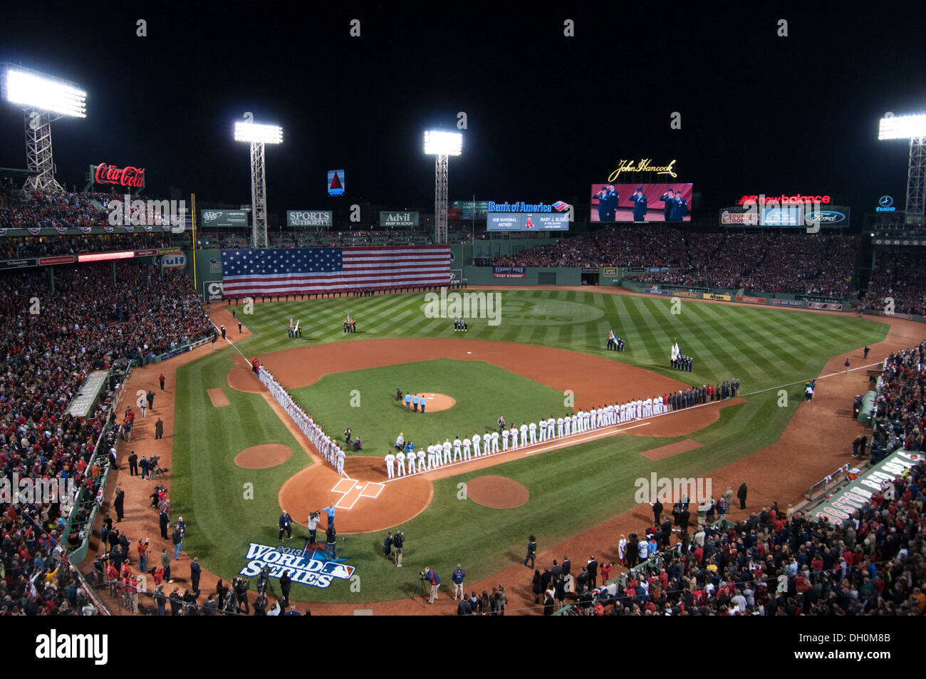 Airmen from Hanscom Air Force Base, also captured on the center-field Jumbotron, line the flag-draped left-field wall at Fenway - Stock Image