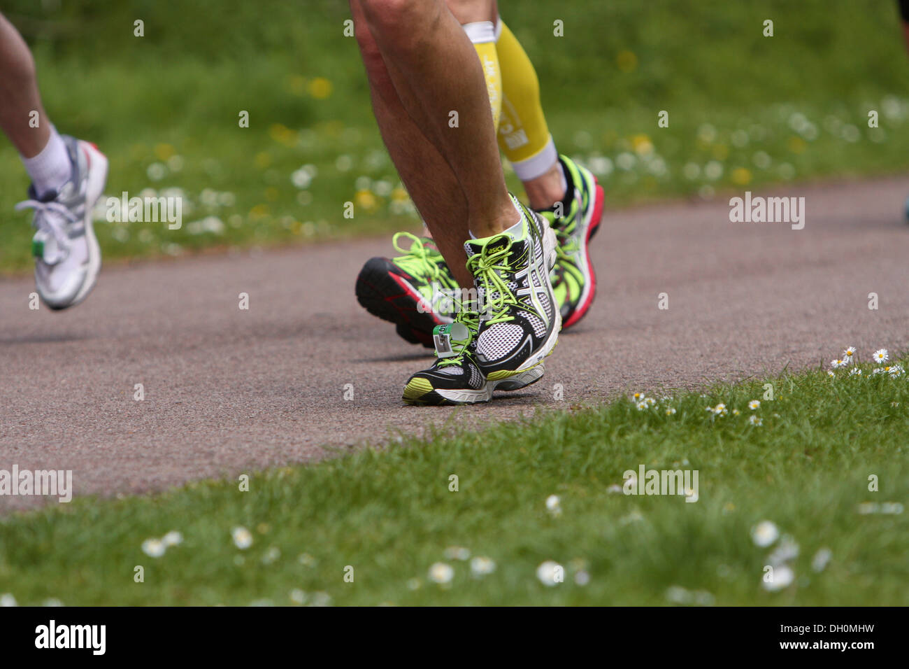 Three 3 marathon runners feet in motion - Stock Image