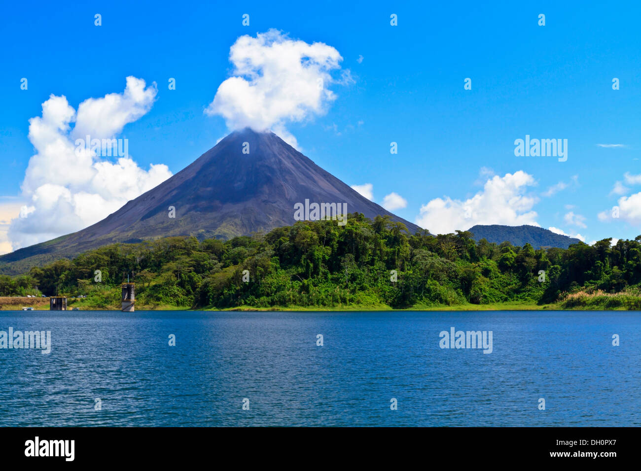 Arenal Volcano 'puffs' out a cloud above the rainforest on the shores of Lake Arenal in Costa Rica - Stock Image