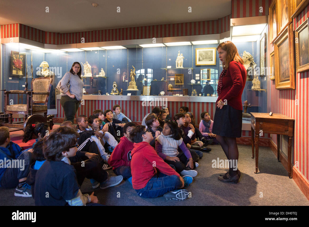 class of schoolchildren listening to teacher on field trip to Carnavalet Museum, Paris, France - Stock Image