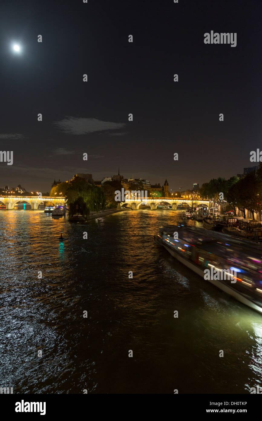 full moon on the Seine with a pleasure boat and a view the Île de la Cité, île St. Louis,  and the Pont Neuf, Paris, France - Stock Image
