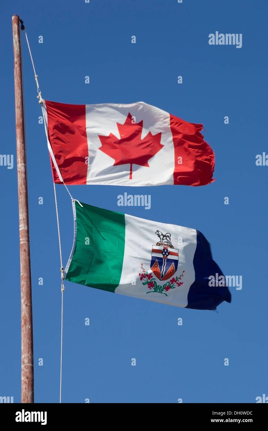 Canadian flag and Yukon territorial flag, in the wind, Yukon Territory, Canada - Stock Image