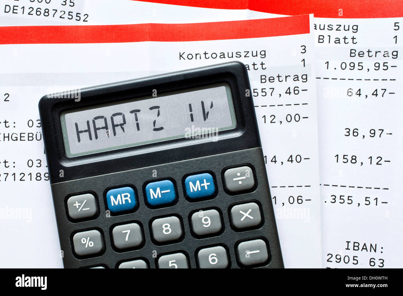 Calculator with the term 'Hartz IV' in the display and bank statements, Germany - Stock Image