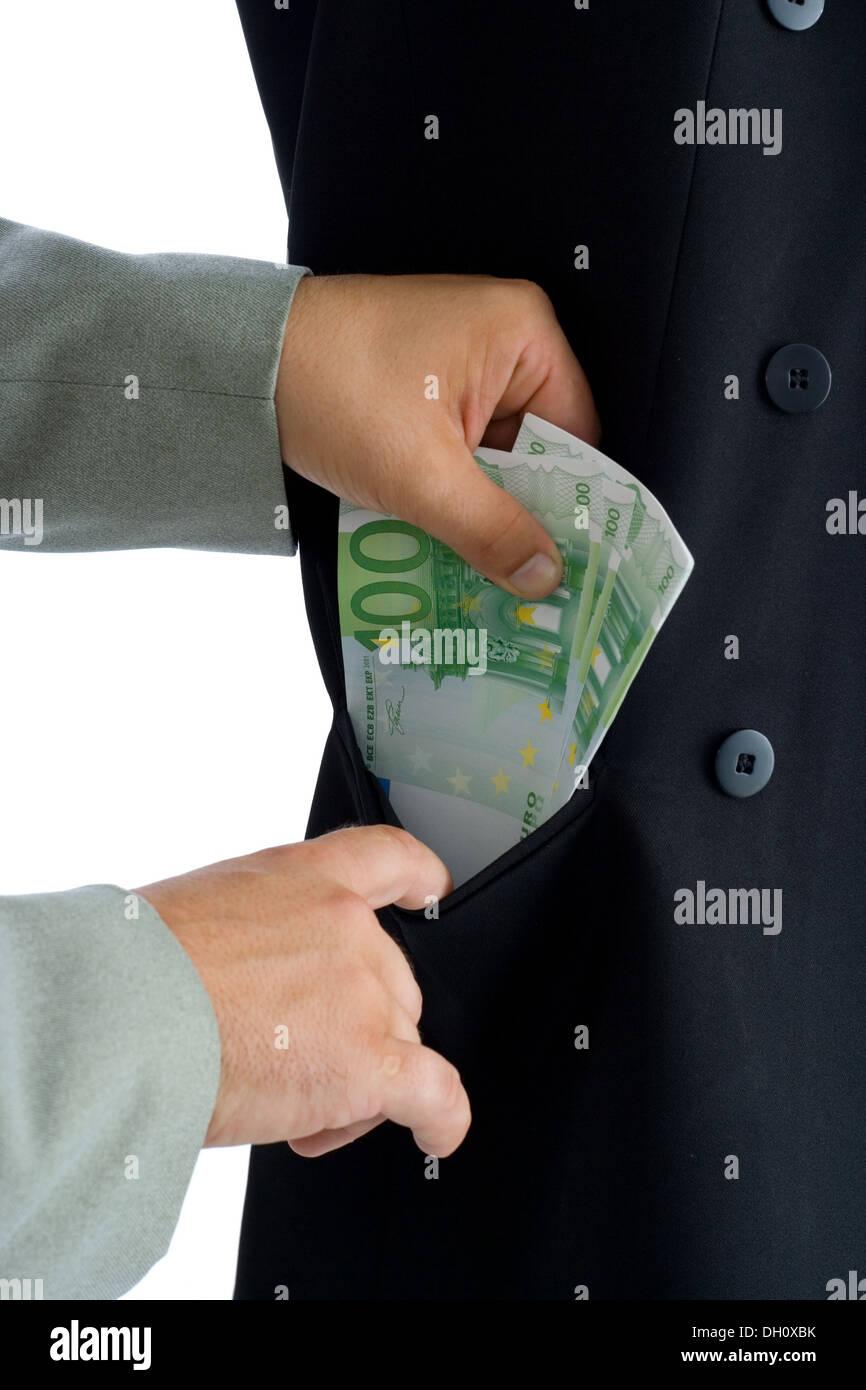 Hands putting several hundred euros into a pocket - Stock Image