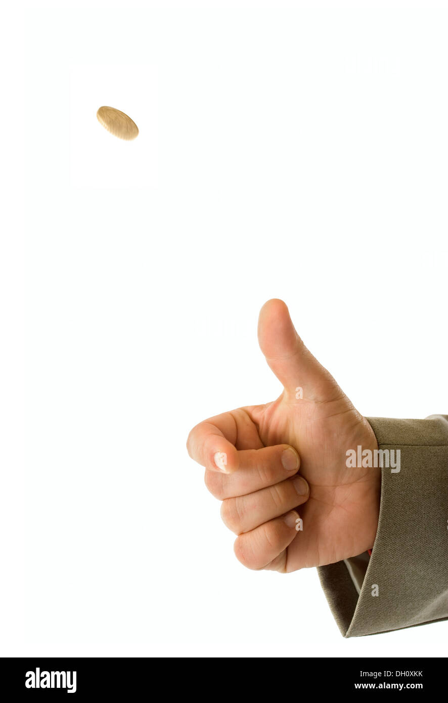 Man's hand throwing up a coin to make a decision - Stock Image