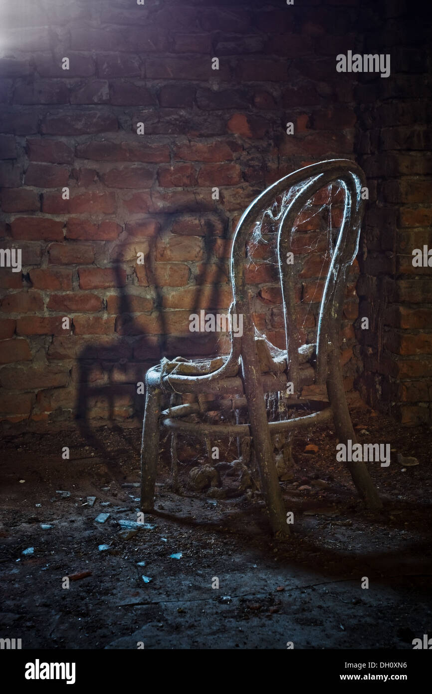 Old chair in light in a haunted house & Old chair in light in a haunted house Stock Photo: 62101234 - Alamy