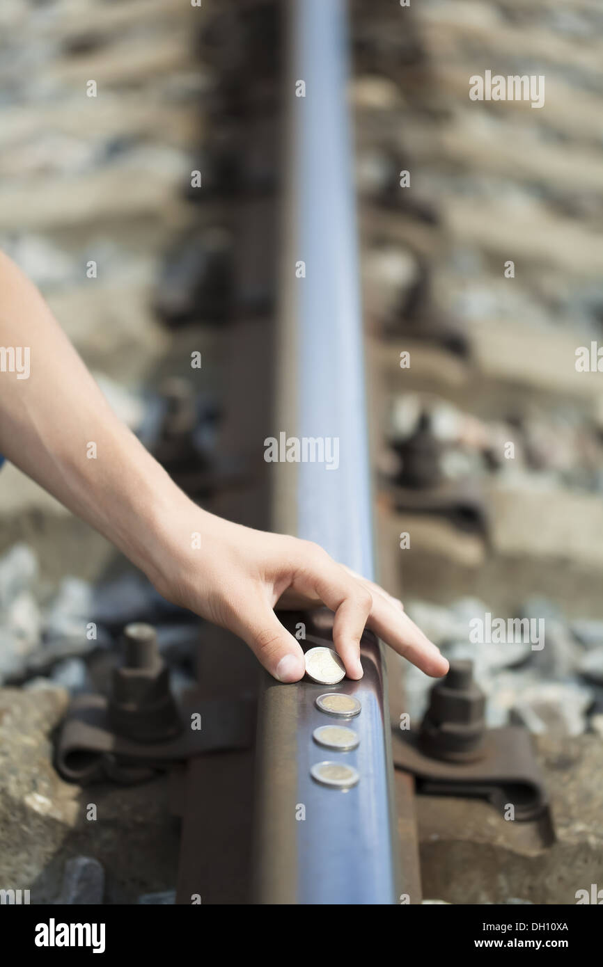 Hand near euro coins on the rails - Stock Image