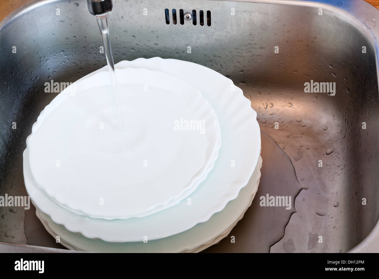 wash-up in metal sink for washing dishes - Stock Image