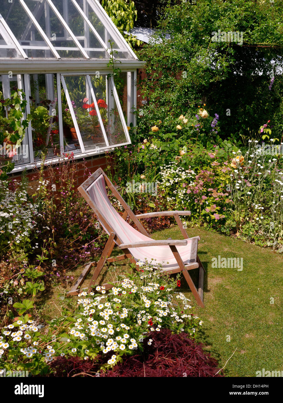 Small lawned garden with borders, deck chair and greenhouse, Barnsdale Gardens, Oakham, Rutland, England, UK. - Stock Image