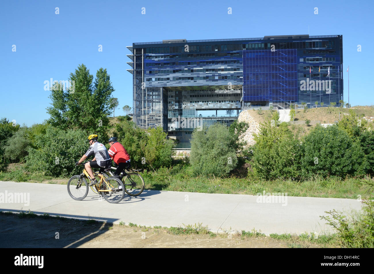 Cyclists Cycle Along Cycle Track in front of Montpellier Town Hall or City Hall by Jean Nouvel Montpellier France - Stock Image