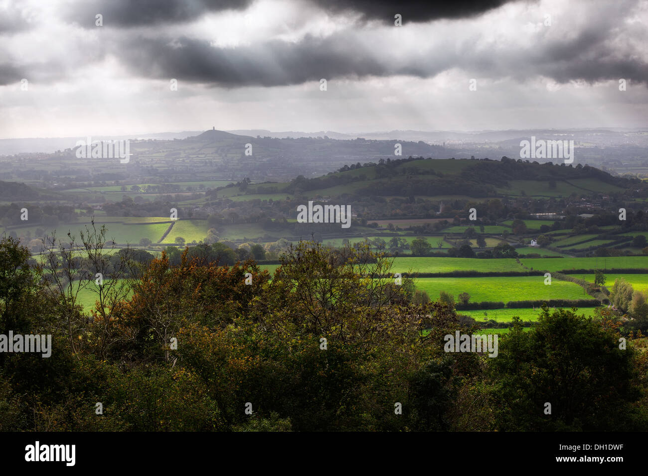 View of the Somerset Levels and Glastonbury Tor in the mist with a dramatic sky - Stock Image