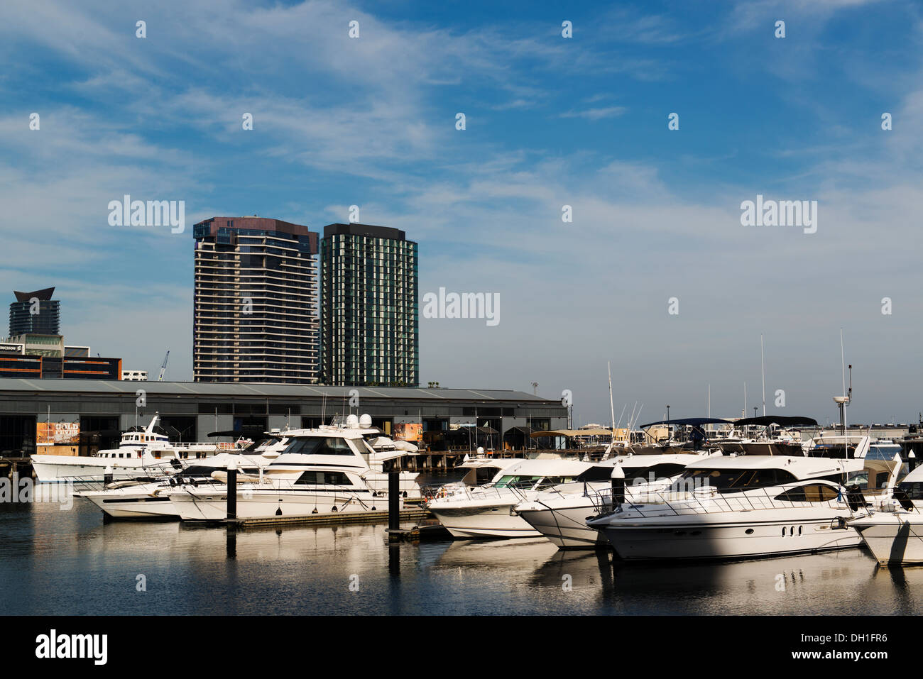 Motor boats moored in Melbourne's Docklands precinct with the apartment buildings beyond. - Stock Image
