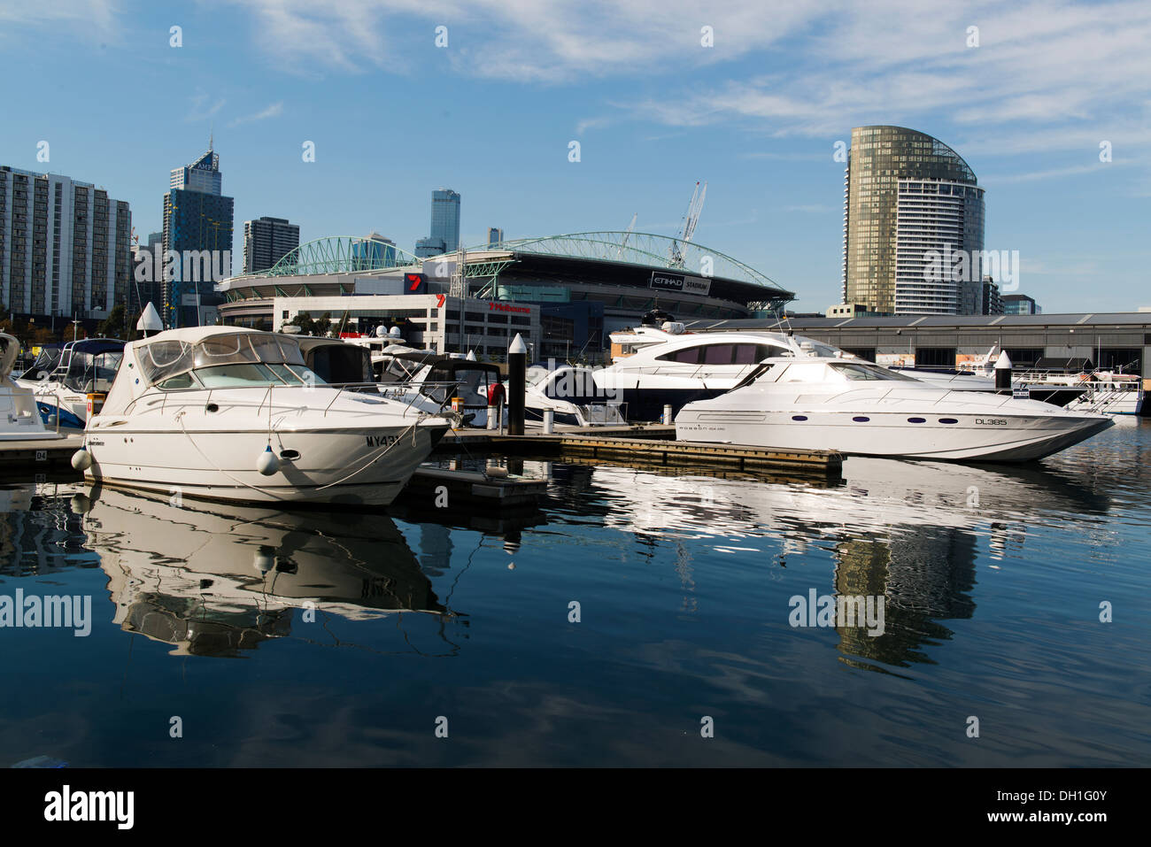 Motor boats moored in Melbourne's Docklands precinct with the city skyline beyond. - Stock Image