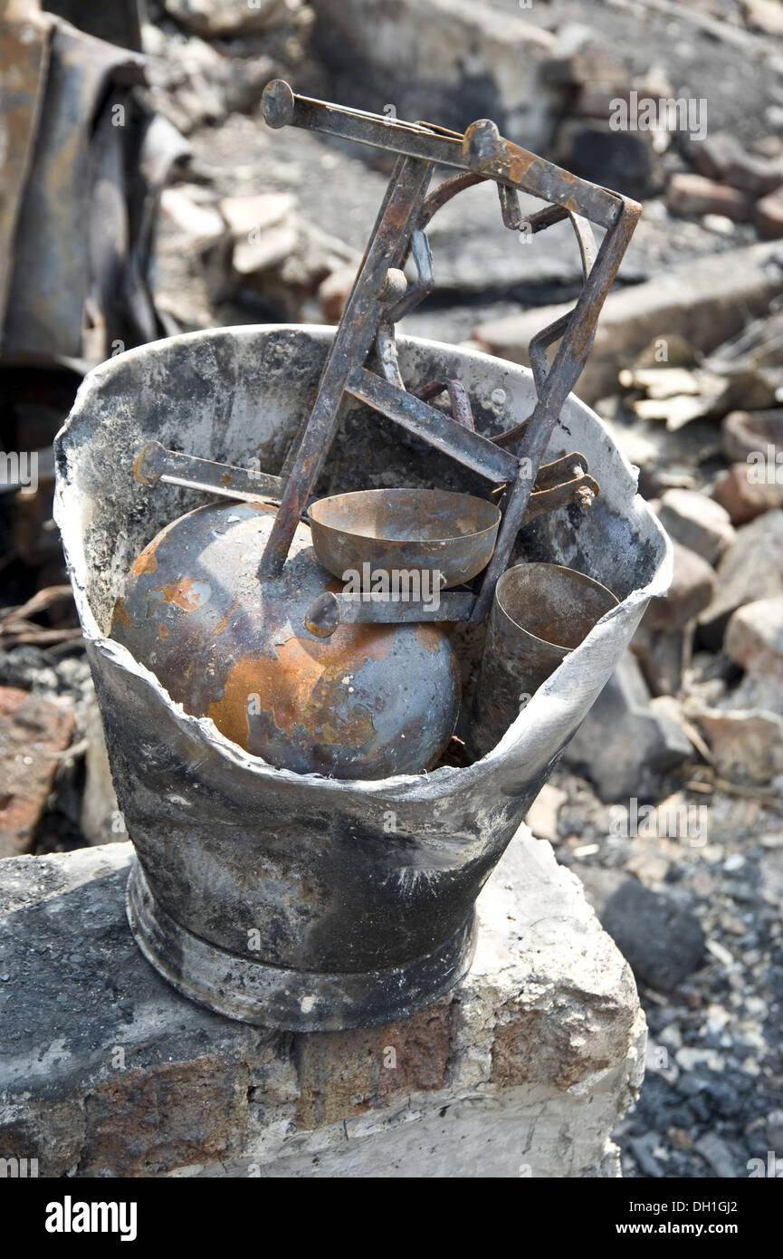 damaged destroyed things in bucket after fire bandra slums mumbai Maharashtra India Asia Stock Photo