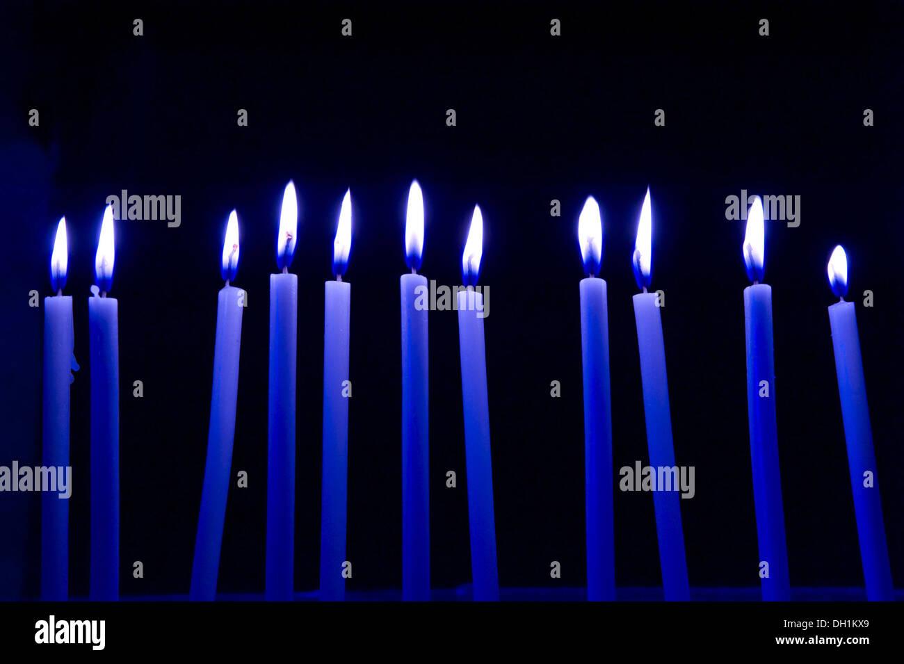 eleven blue candles burning flame black background - Stock Image