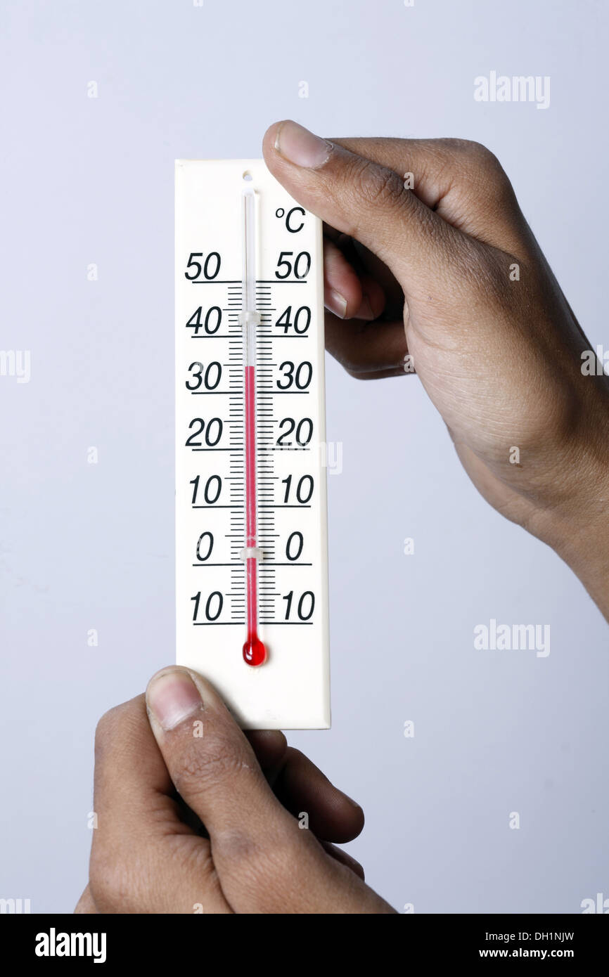 Weather temperature meter showing 35 degrees celsius centigrade close up of Temperature meter holding in both hands MR#743AE - Stock Image