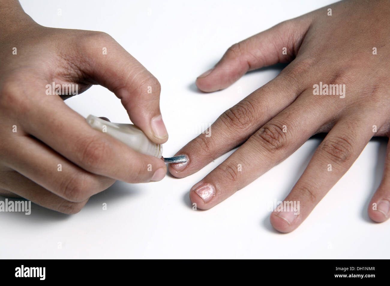 Young girl woman applying nail polish on finger close up of fingers and nail polish brush   MR#743AC Stock Photo