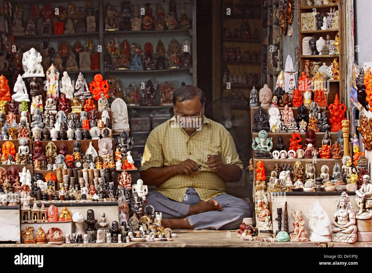 shopkeeper selling idols of Hindu Gods Goddesses Varanasi Uttar Pradesh India - Stock Image