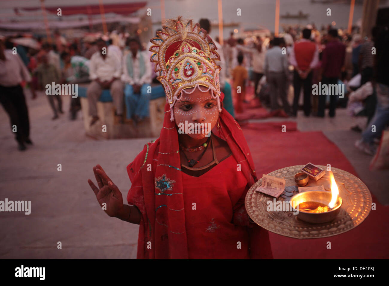 young boy dressed as Hindu God seek alms on ghats of Ganga River ganges varanasi Uttar Pradesh India - Stock Image