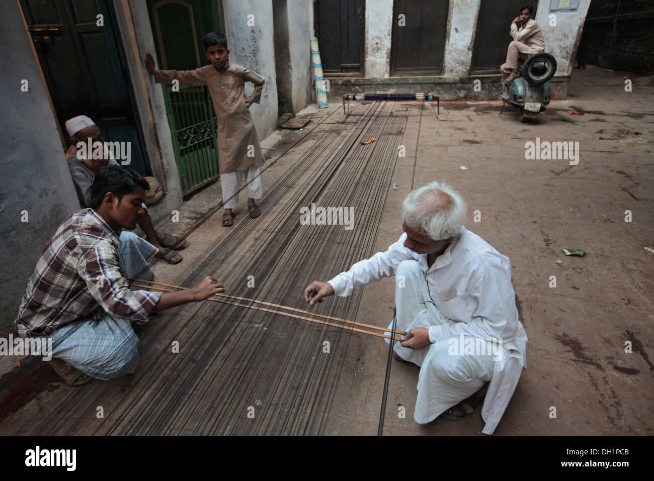 weavers preparing warp thread for weaving Banarasi sarees Varanasi Uttar Pradesh India - Stock Image